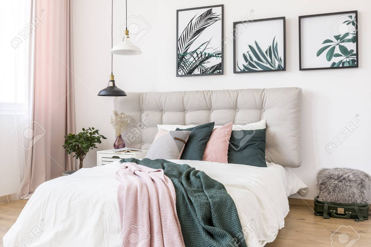 Black and white lamp above bed with pink and green blanket against..
