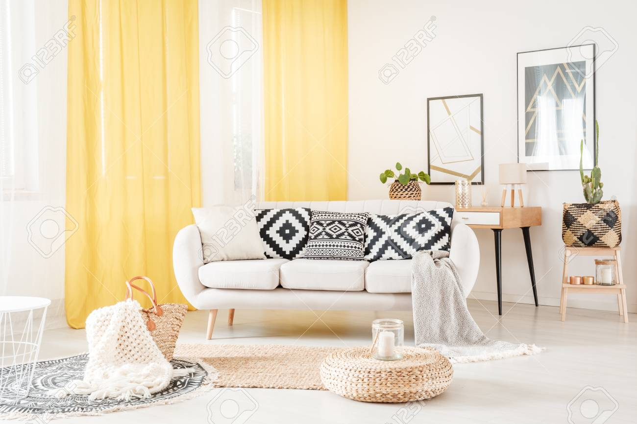Pillows with geometric pattern lying on a white sofa in cozy..
