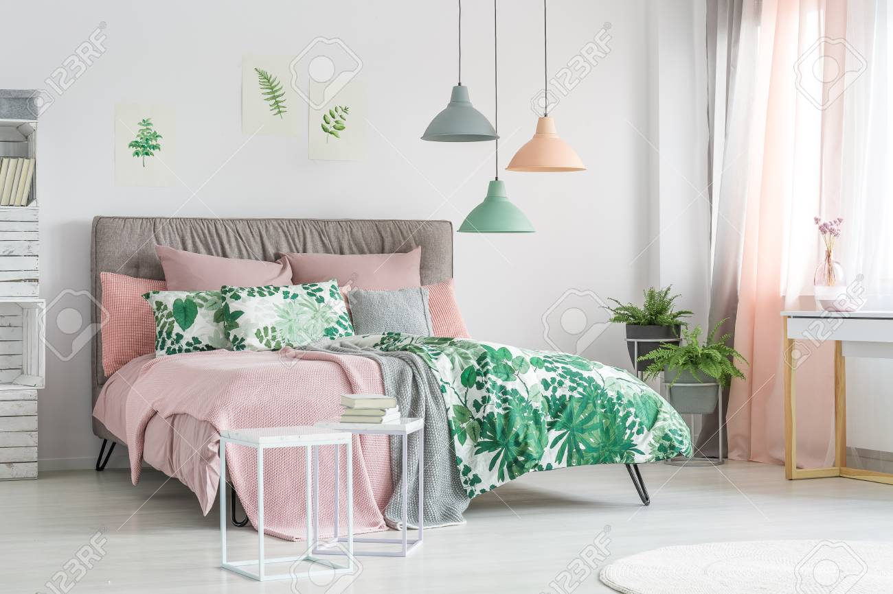 Pastel bedding on stylish bed in white bedroom with plants
