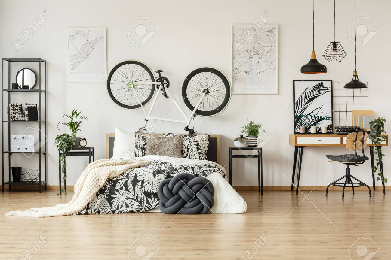 Wooden chair against desk in trendy black and white bedroom for..