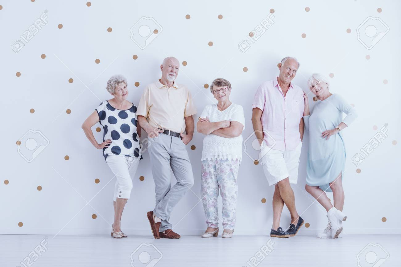 Smiling Seniors In Casual Clothes Against White Wallpaper With Gold Dots Stock Photo