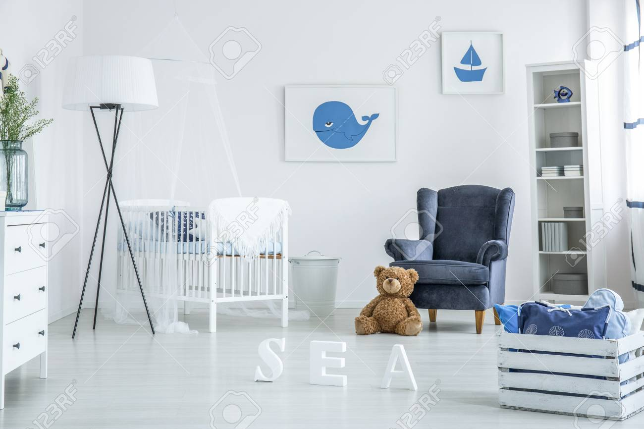 photo cozy white and blue nursery with suede armchair and whale poster over a wooden crib