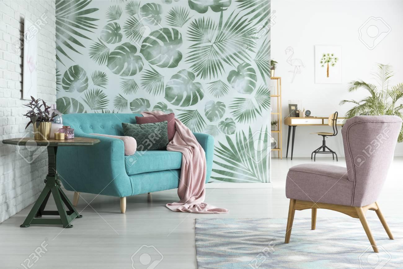 Fauteuil rose pastel debout devant un canapé bleu avec une couverture rose  dans l & # 39 ; intérieur intérieur du salon ouvert