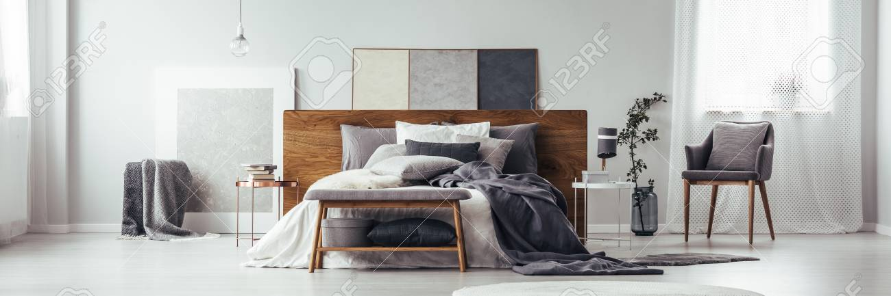 Stock Photo - Wooden bench and grey chair near king size bed in monochromatic bedroom interior with paintings and window & Wooden Bench And Grey Chair Near King Size Bed In Monochromatic ...