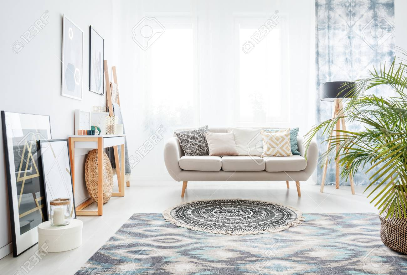 Round Rug With Black And White Pattern In Front Of A Beige Sofa