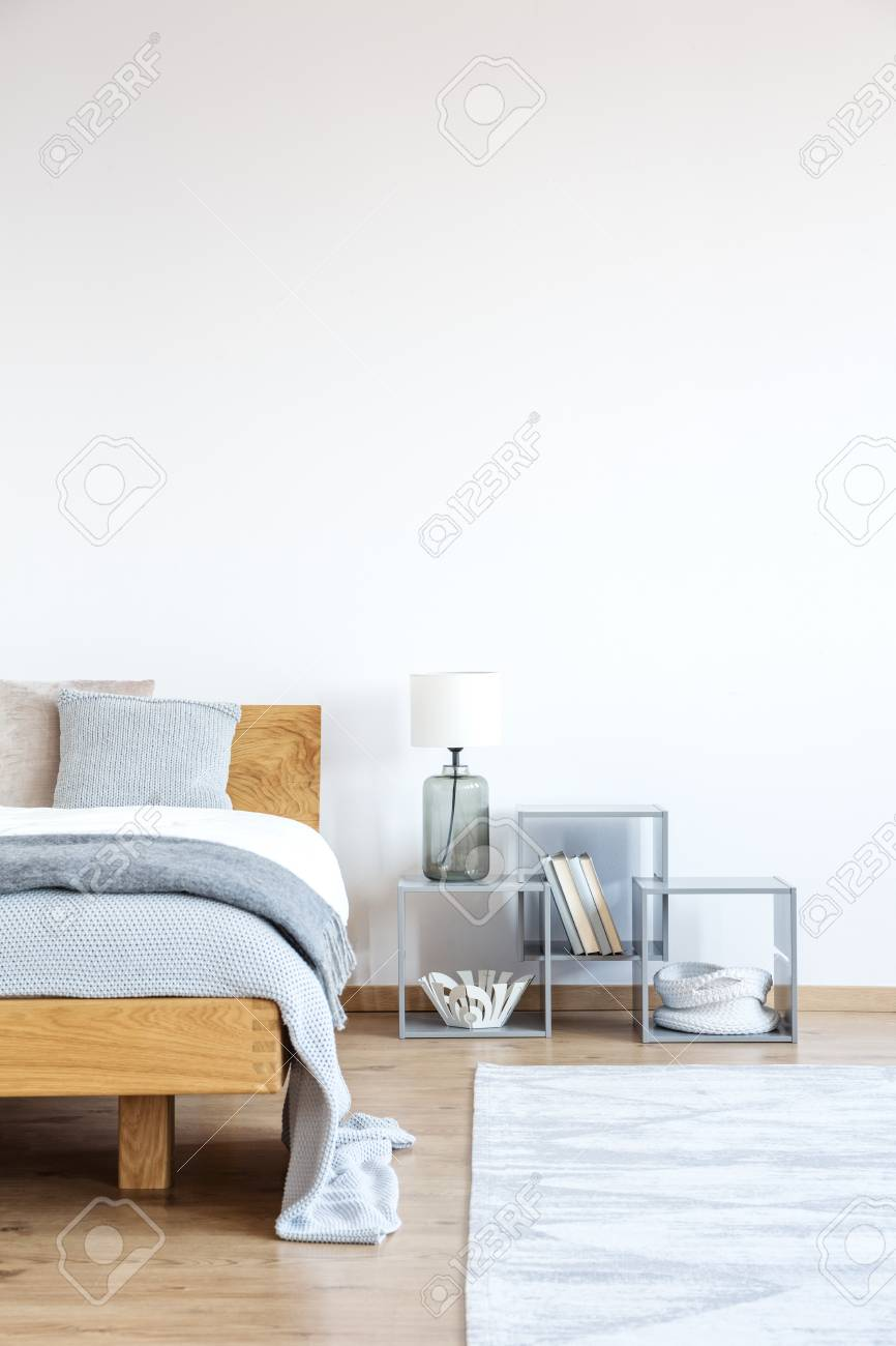 Lamp And Books On Shelves Next To A Wooden Bed With Blue Bedding Stock Photo Picture And Royalty Free Image Image 93510676