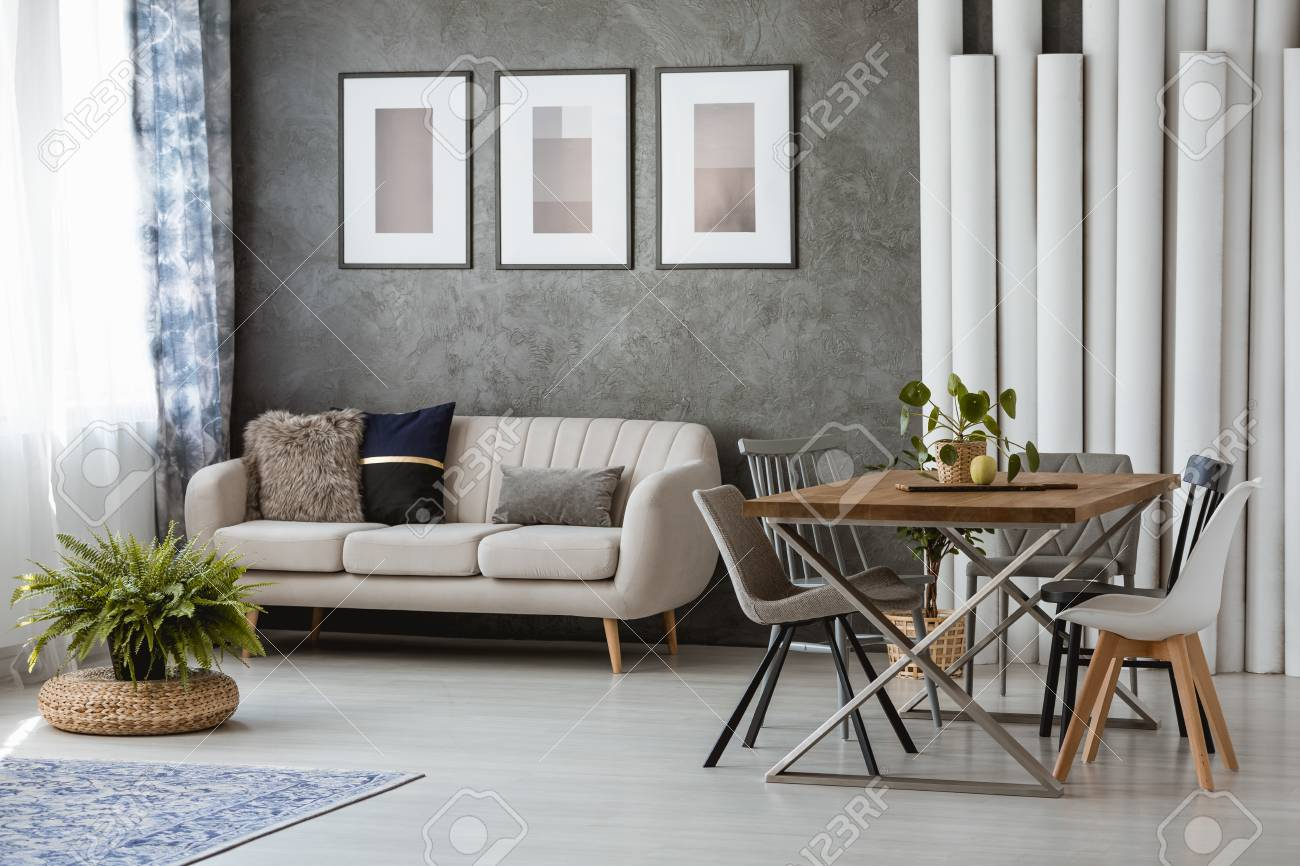 Astounding Posters On Gray Wall Above Beige Couch In Simple Open Room With Dailytribune Chair Design For Home Dailytribuneorg