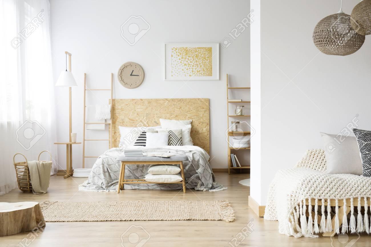 Geraumiges Bohmisches Schlafzimmer Mit Holz Decken Und Bett Gegen Eine Wand Mit Gelber Malerei Und Uhr Lizenzfreie Fotos Bilder Und Stock Fotografie Image 93533089