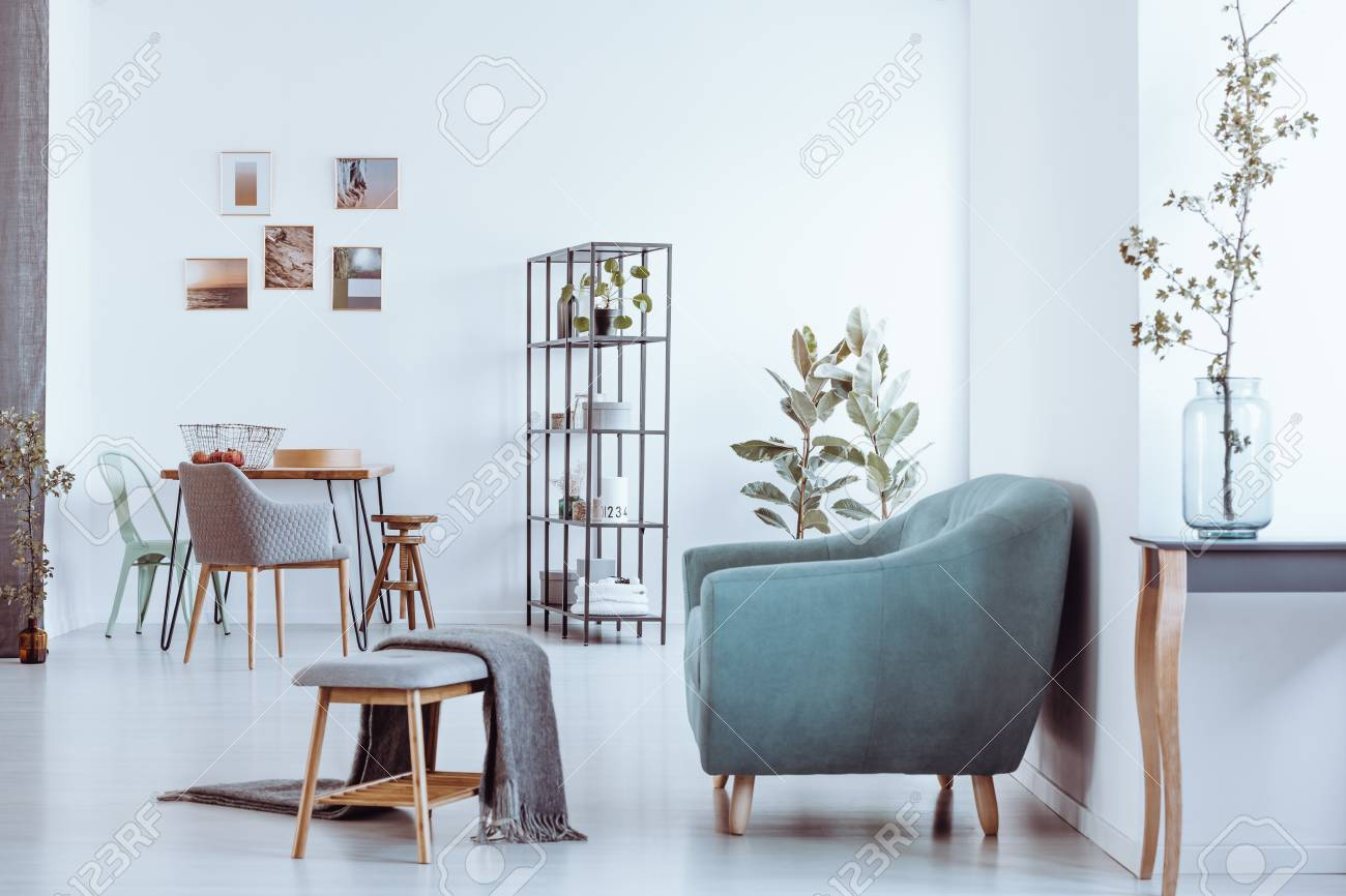 Blanket On Bench And Grey Armchair In Bright Room With Chairs At Dining  Table Against Wall