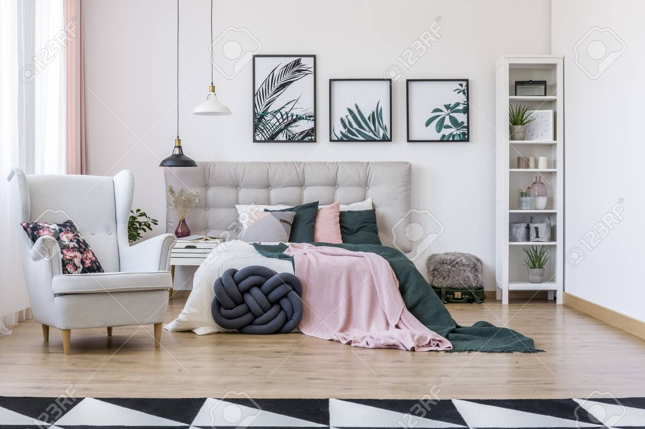 Knot pillow near bed with pink and green bedding near grey armchair..