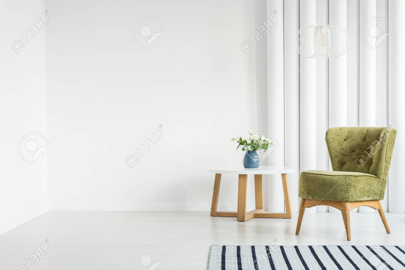 White living room interior with green armchair next to a wooden..