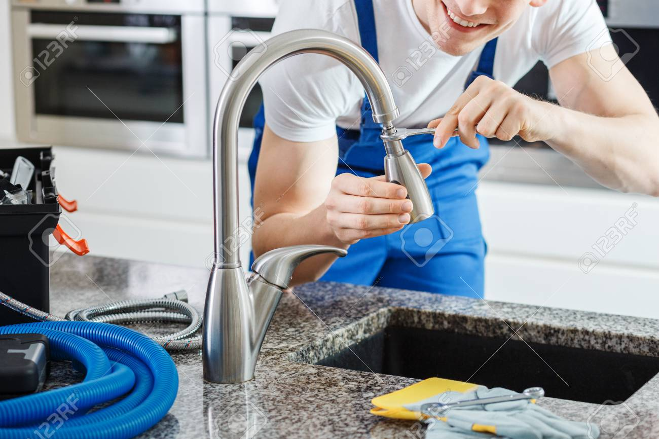 Close-up of smiling plumber fixing a faucet with blue pipes on the countertop - 93782646