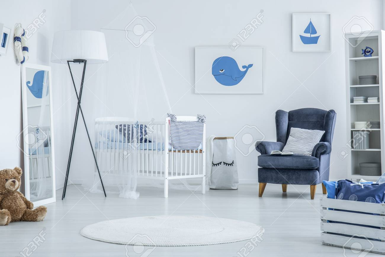 White Interior Of Marine Baby Room Furnished With Wooden Crib