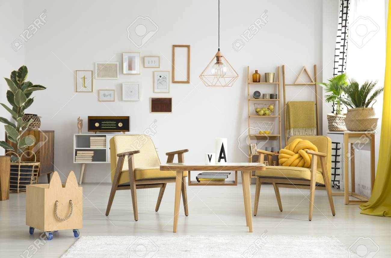Stock Photo   Wooden Box Next To Vintage Armchairs And Table In Living Room  Interior With Copper Lamp, Plants And Gallery Of Posters