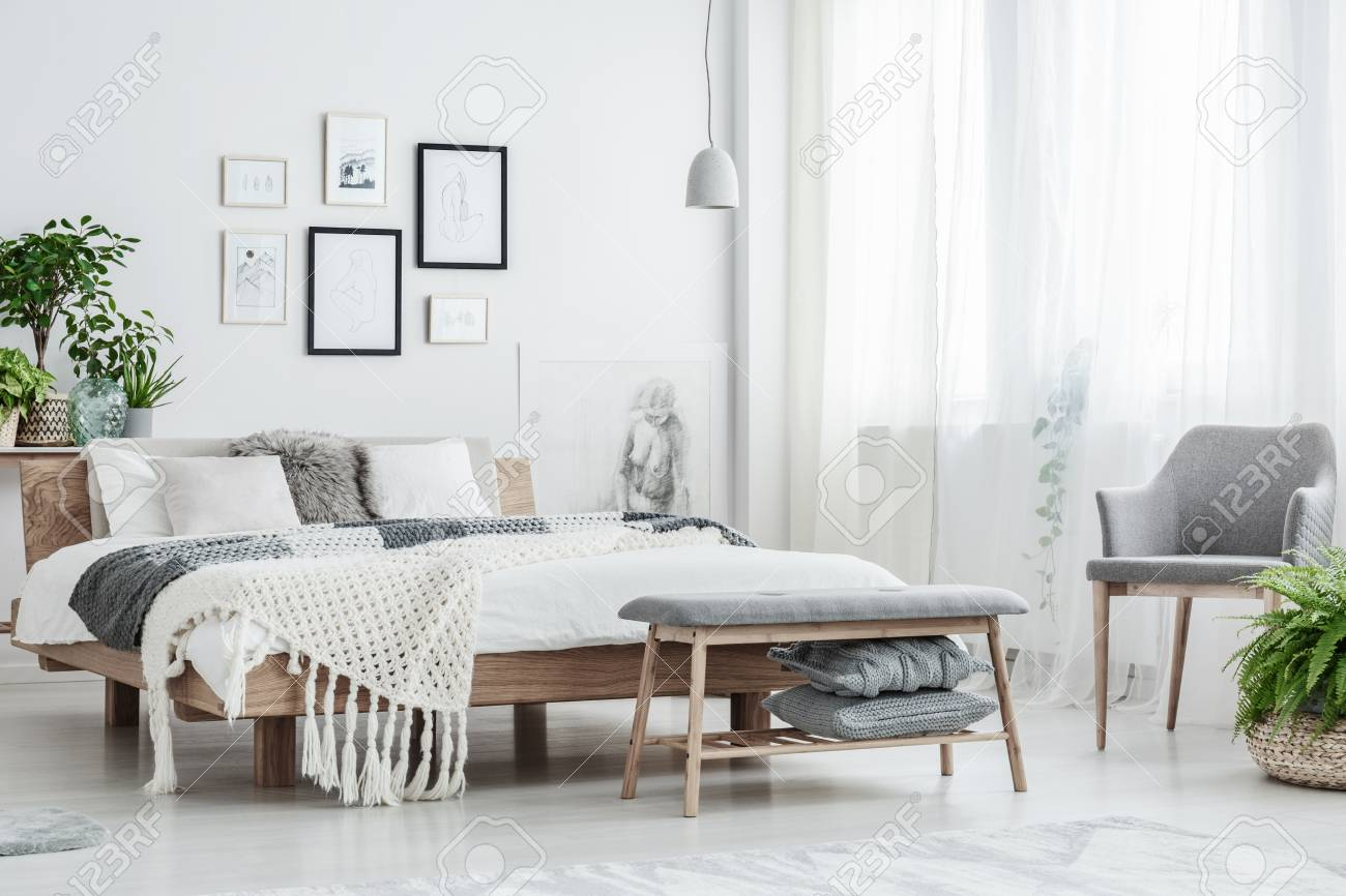 Grey chair and bench in white natural bedroom with cushions on..