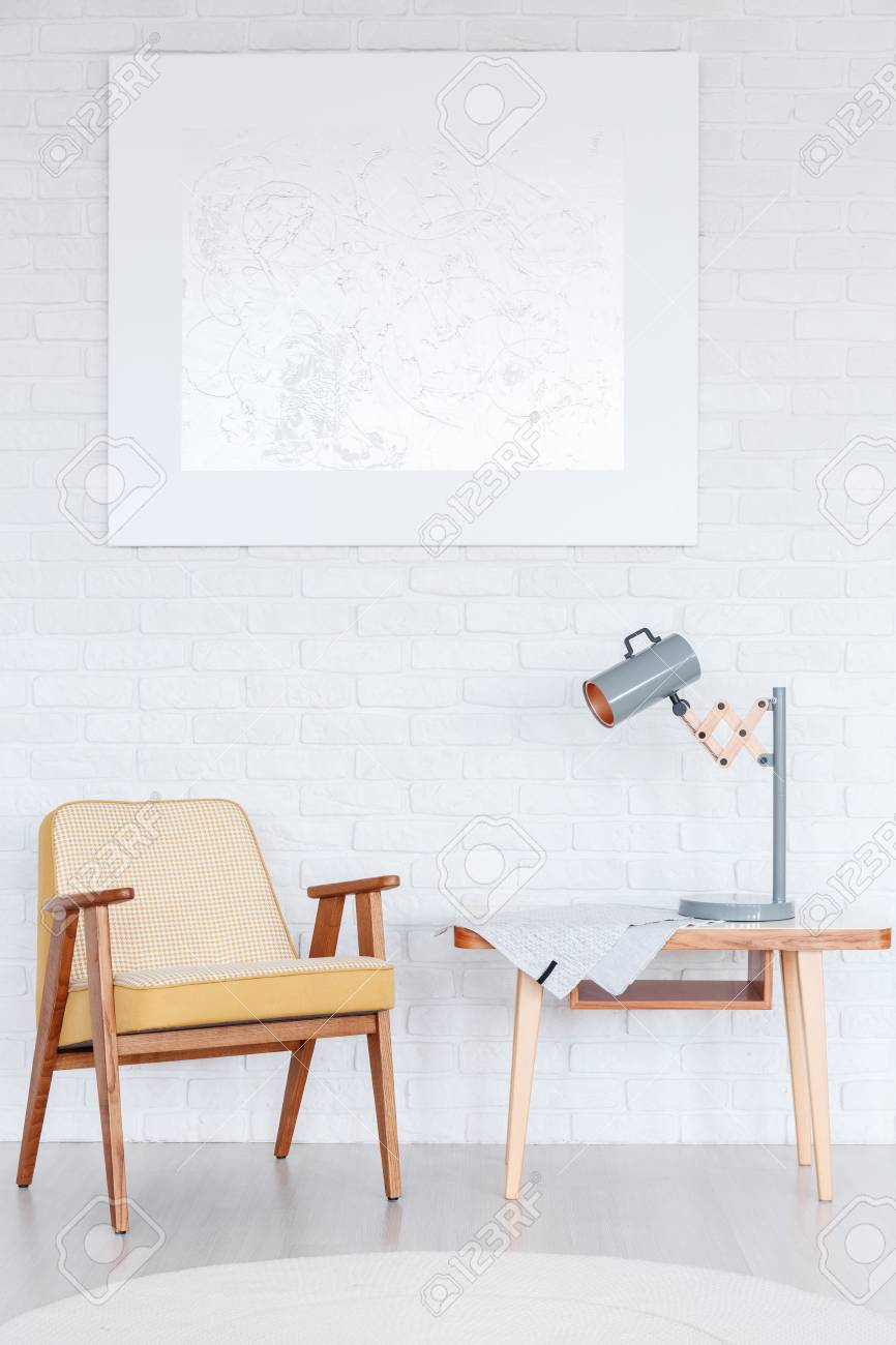 Lamp On Wooden Table Next To Yellow Armchair Against White Wall