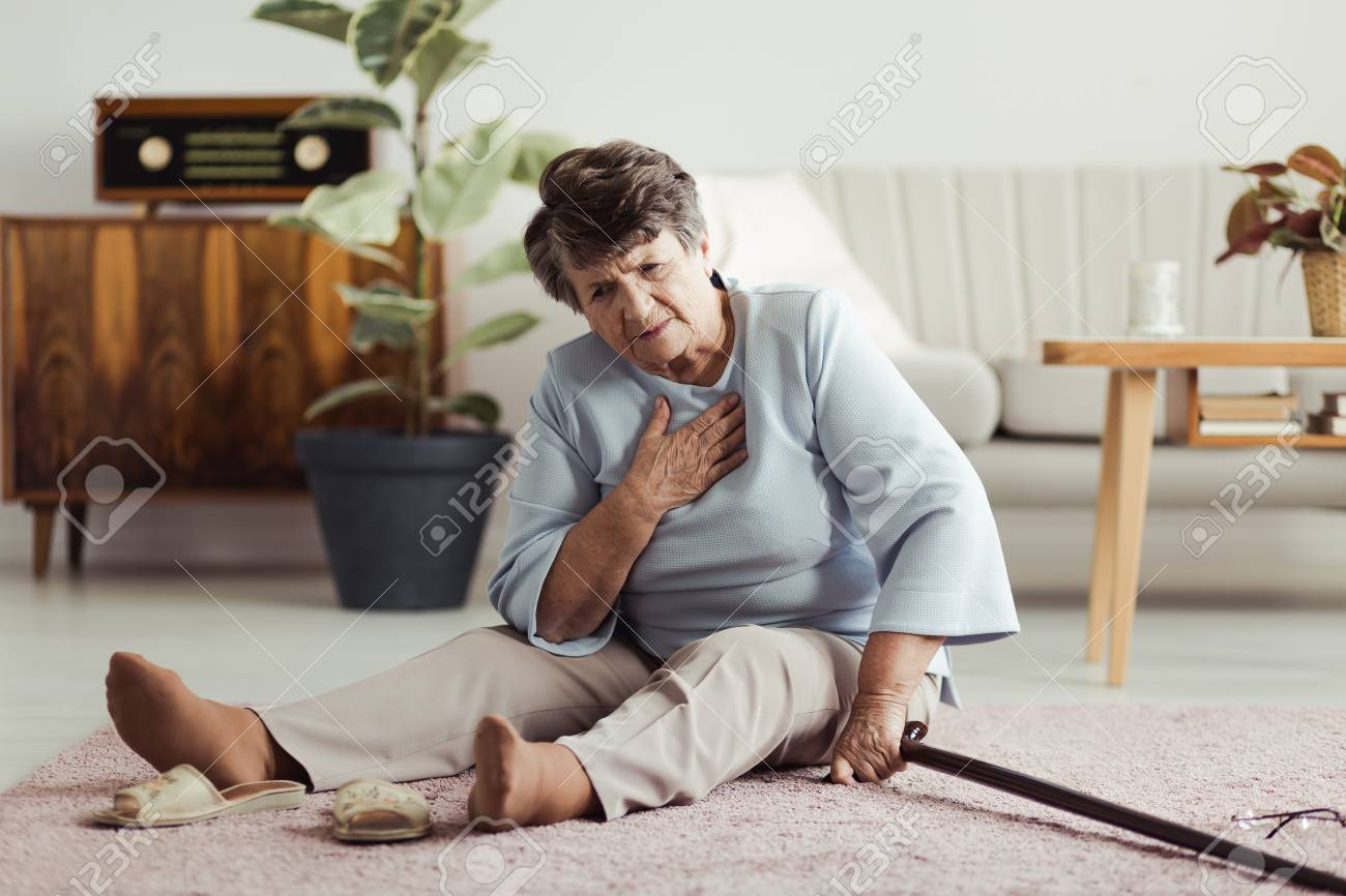 Disabled elder lady sitting on the floor with a walking stick and holding her chest after falling down - 93950901