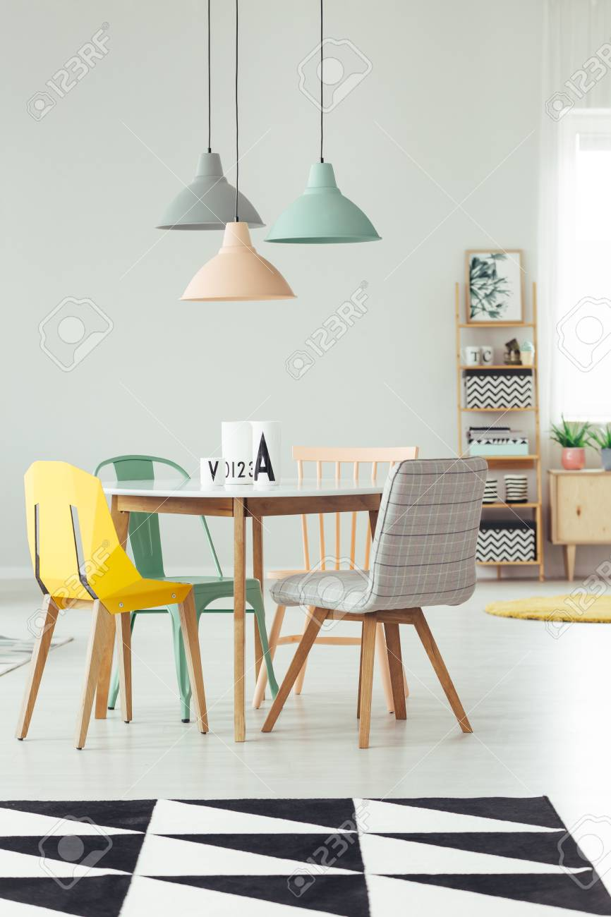 Peach, mint and grey lamp above round table and yellow chair in dining room interior with black and white carpet - 93964269
