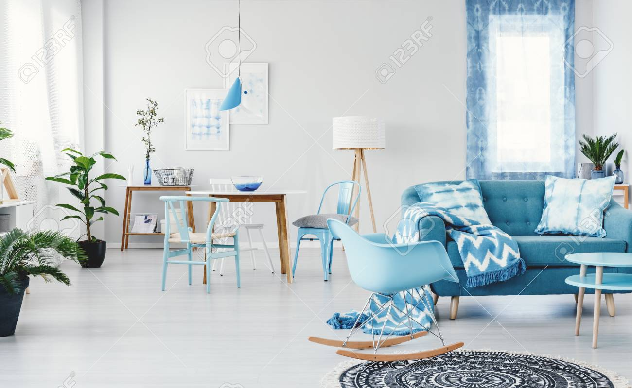 Blue Rocking Chair Next To Sofa With Patterned Blanket In Spacious ...