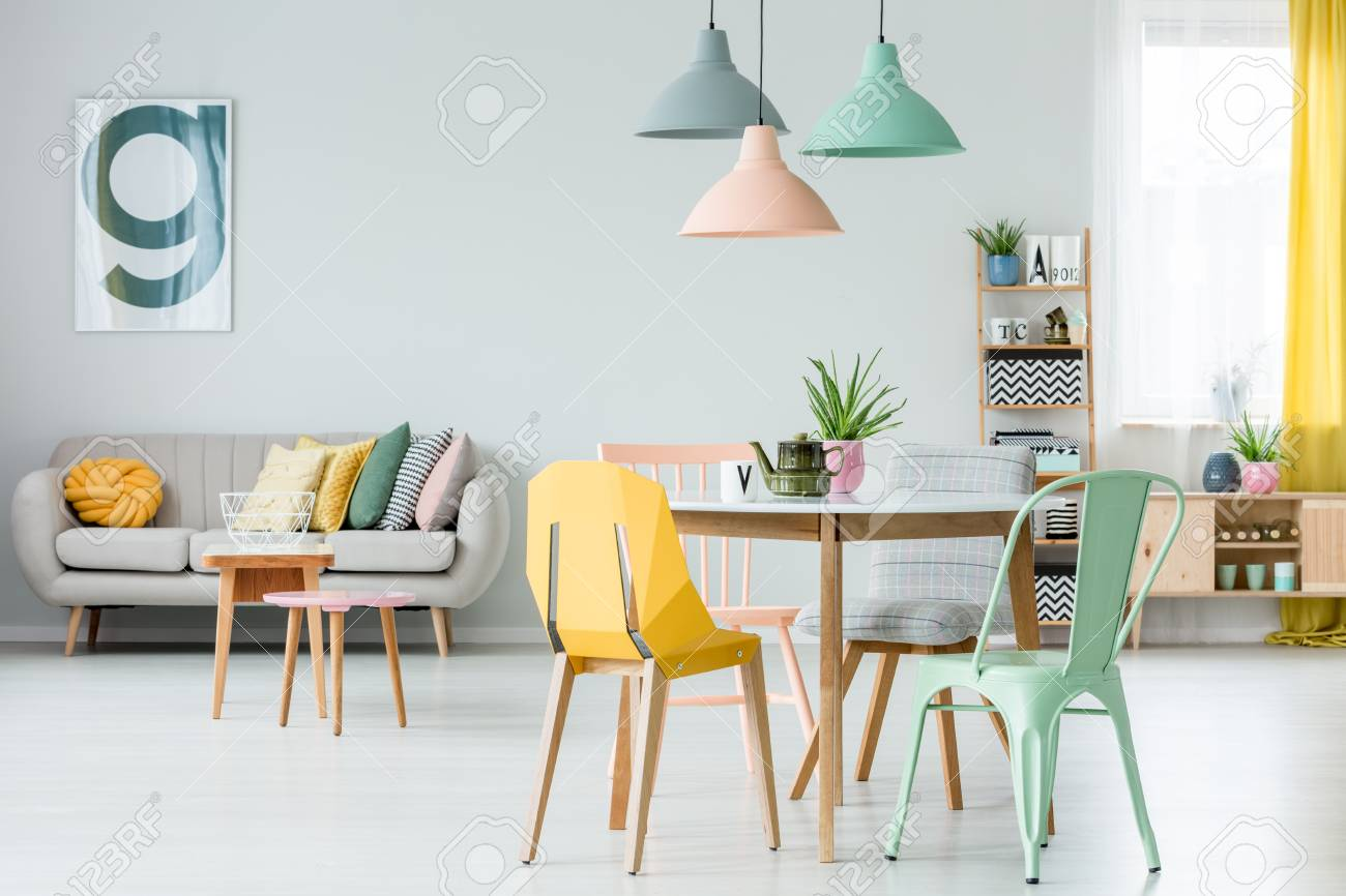 Modern colorful chairs at dining table under pastel lamps in..