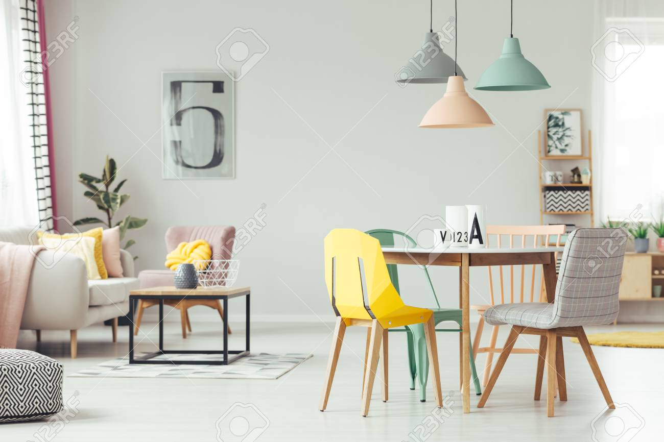 Colorful lamps above wooden table and chairs in yellow living..