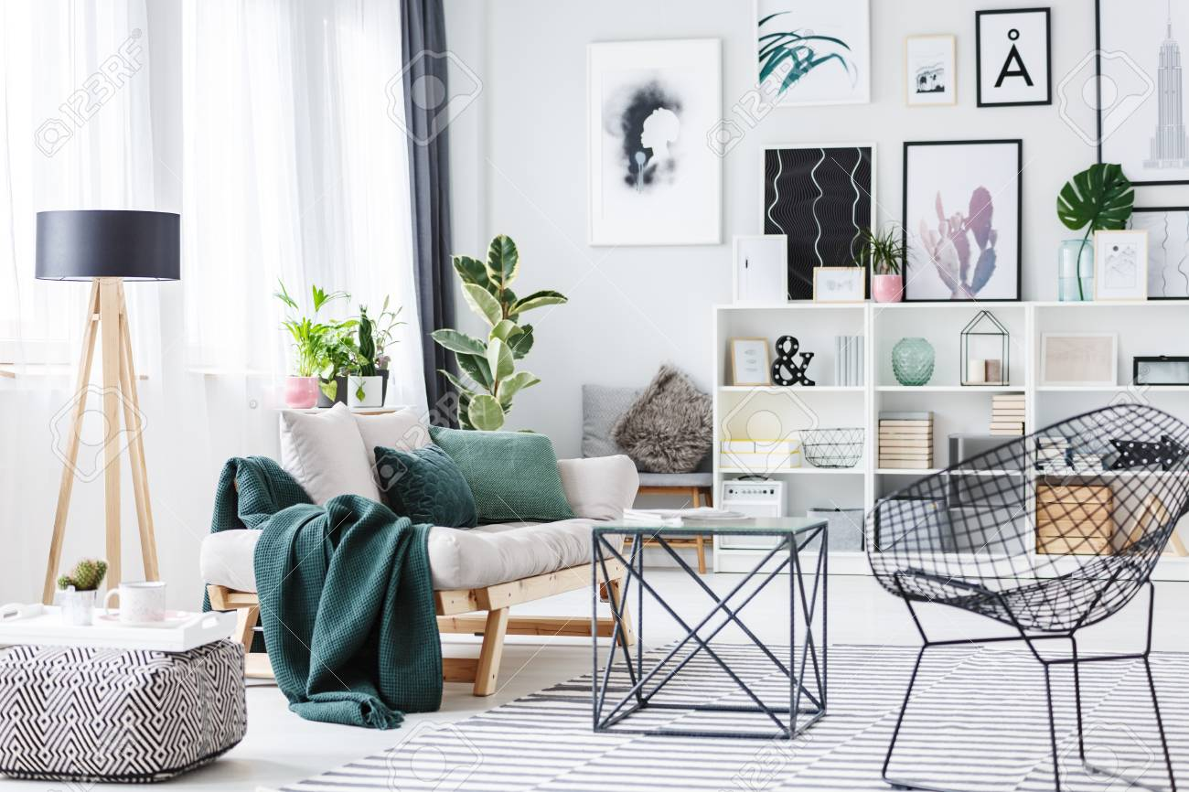 Black chair near a table, pouf and settee with green cushions..