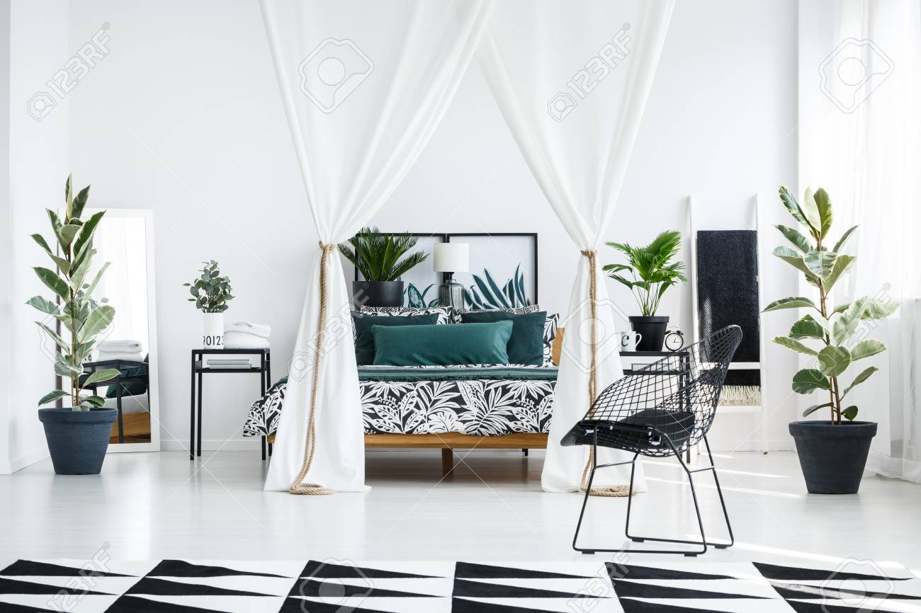 Geometric carpet and black metal chair in spacious white bedroom..