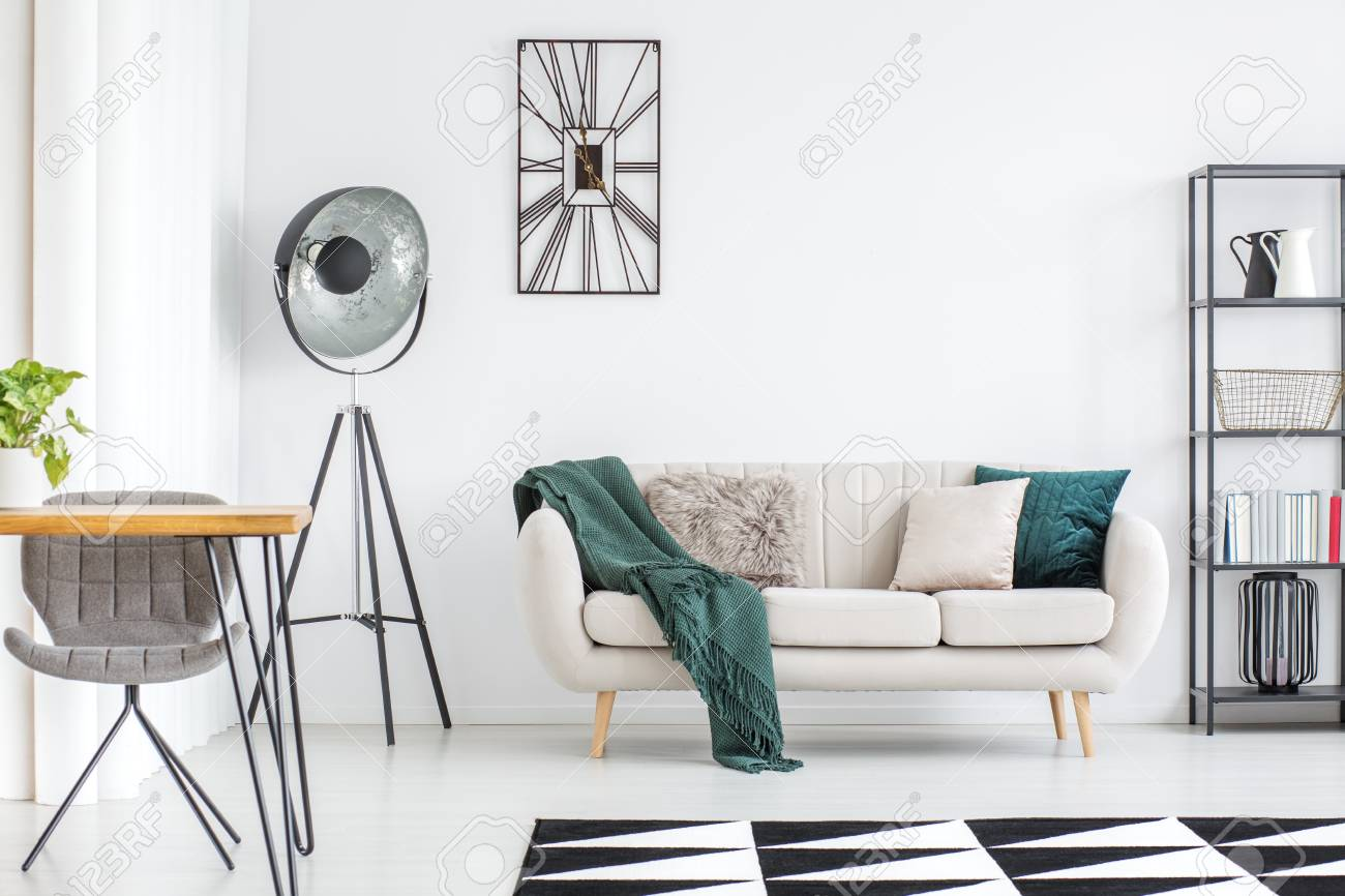 Dark green blanket on cream sofa and black lamp in modern living..