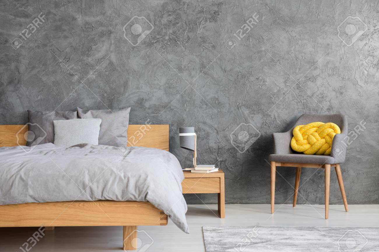 photo grey bedroom interior with king size bed armchair and yellow knot cushion