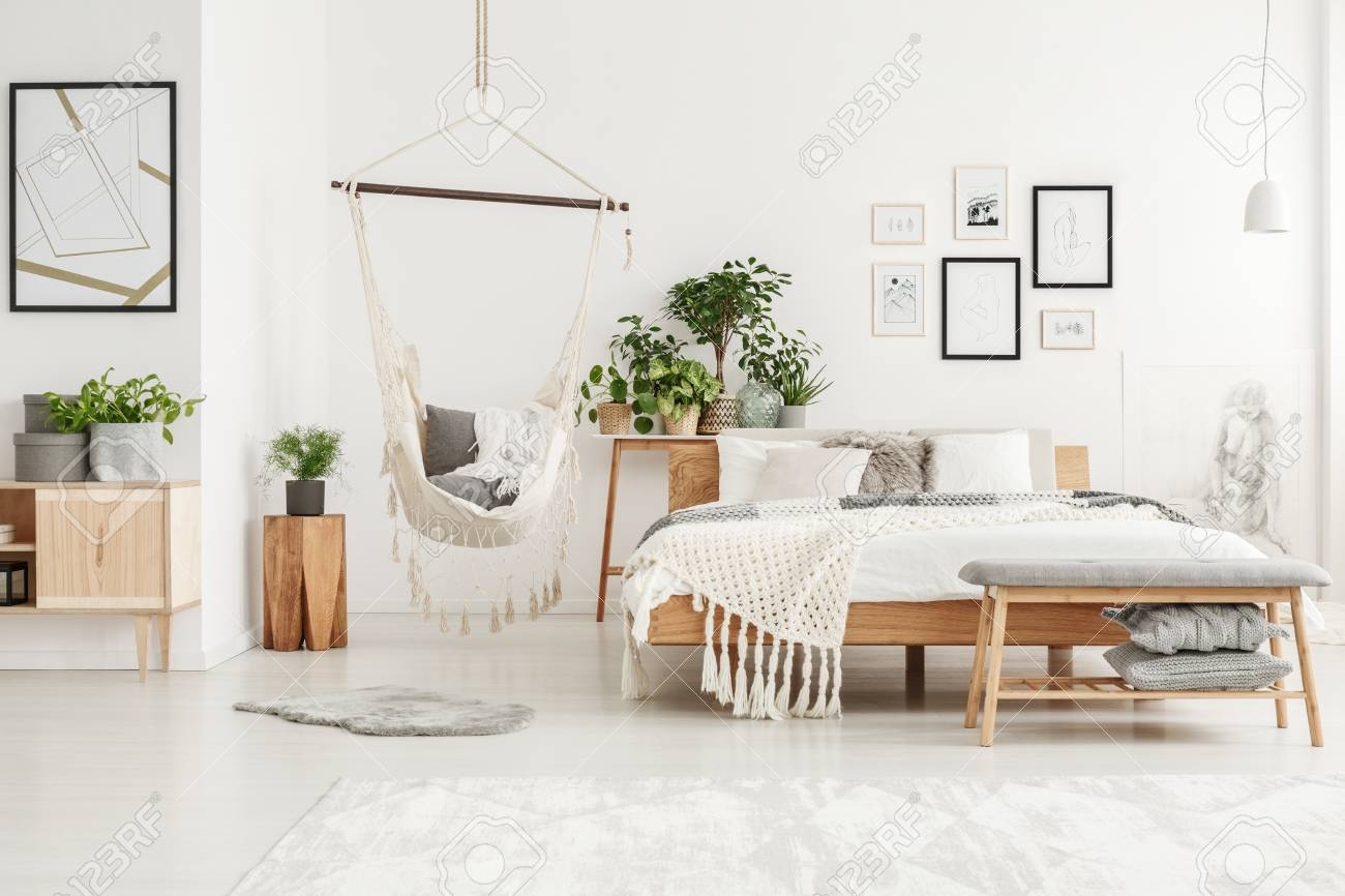 White and beige bedroom interior with plant on wooden stool and..