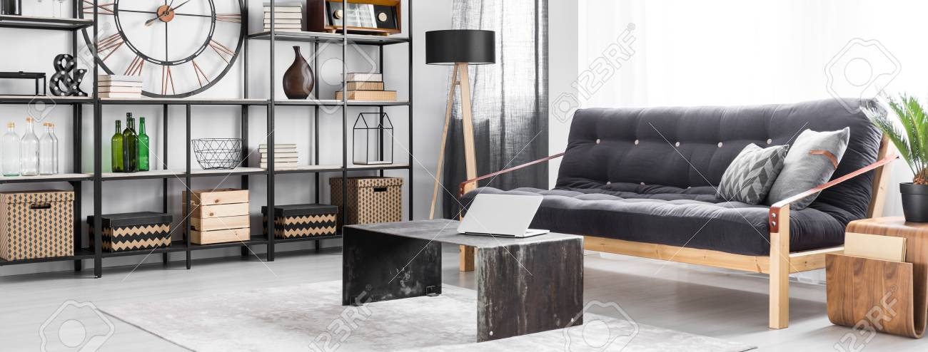 Metal table with silver laptop on grey carpet in man\'s living..