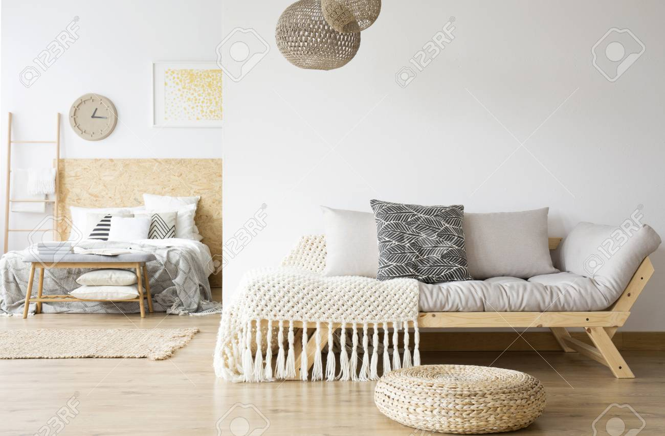 Open design of modern apartment with gray couch in the living room and wooden bed in the bedroom - 94108644