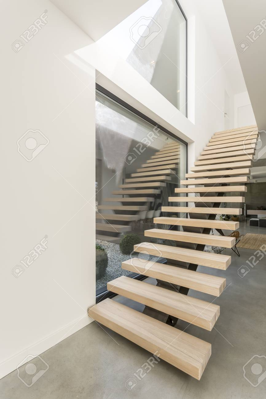 Designed Wooden Stairs Next To Huge Window In Spacious White Apartment With  View On Terrace Stock
