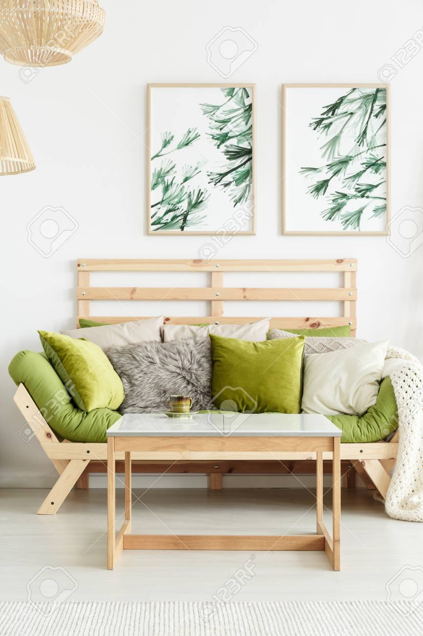 Close Up Of Wooden Sofa With Green Cushions Standing Against
