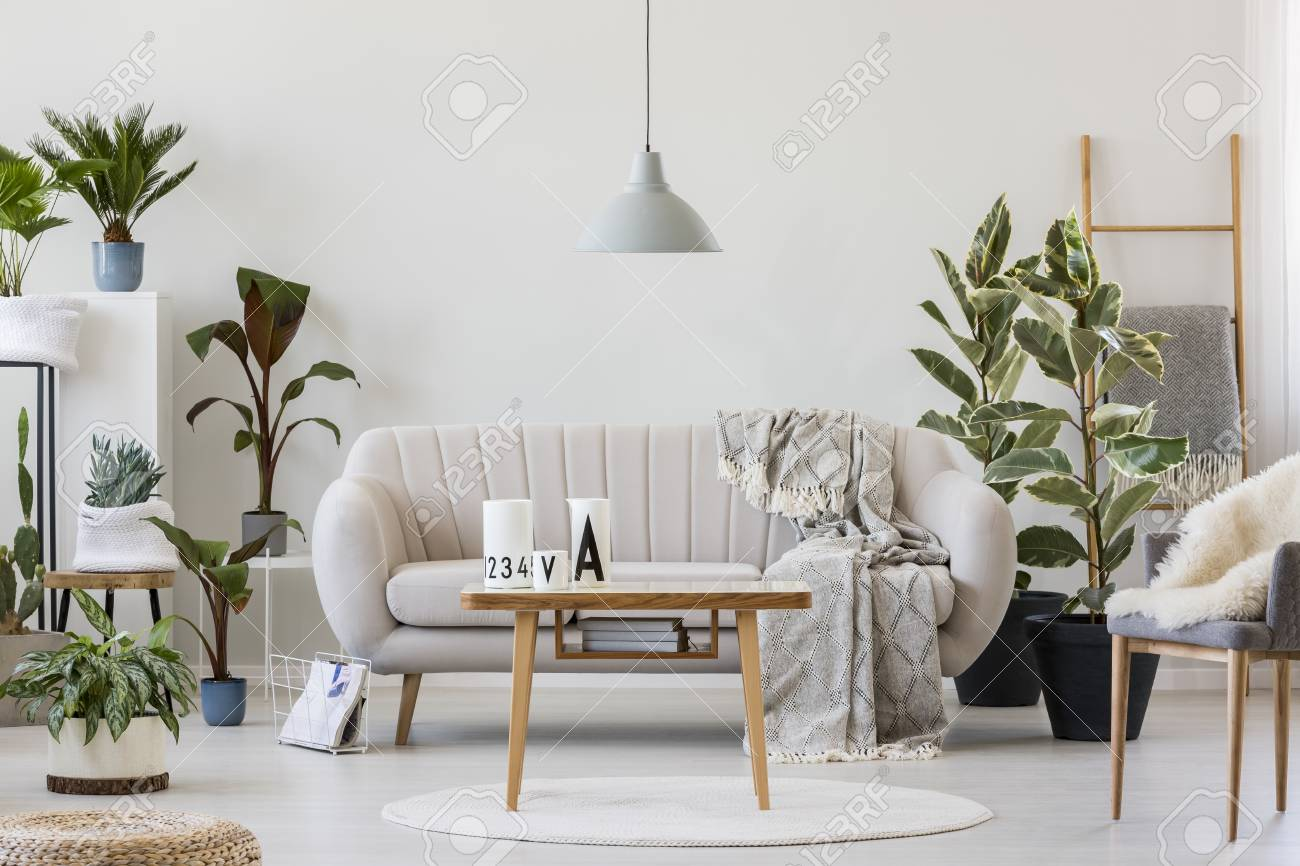 Gray lamp above wooden table near beige sofa in cozy living room..
