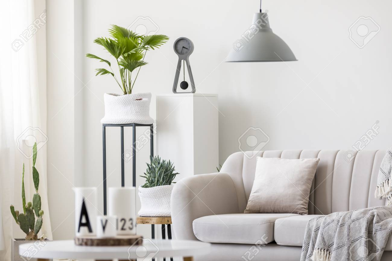 Gray lamp above beige couch with pillow in bright living room..