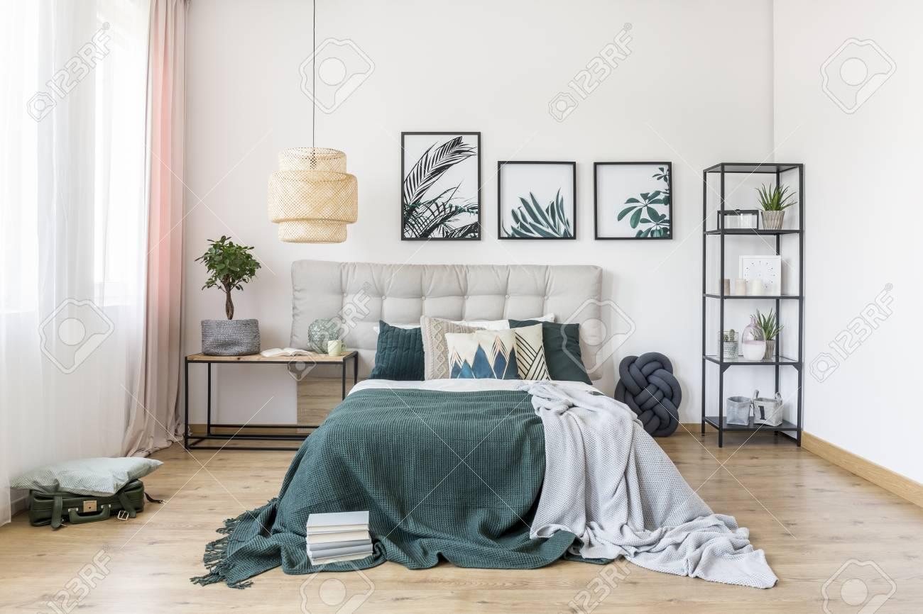 Couverture grise et vert sur le lit contre le mur blanc avec des affiches  dans la chambre intérieure avec la décoration et lampe