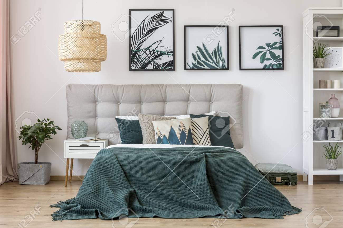 Lampe de rotin lit lit avec literie verte et gris coin dans une chambre  intérieur avec des feuilles de table