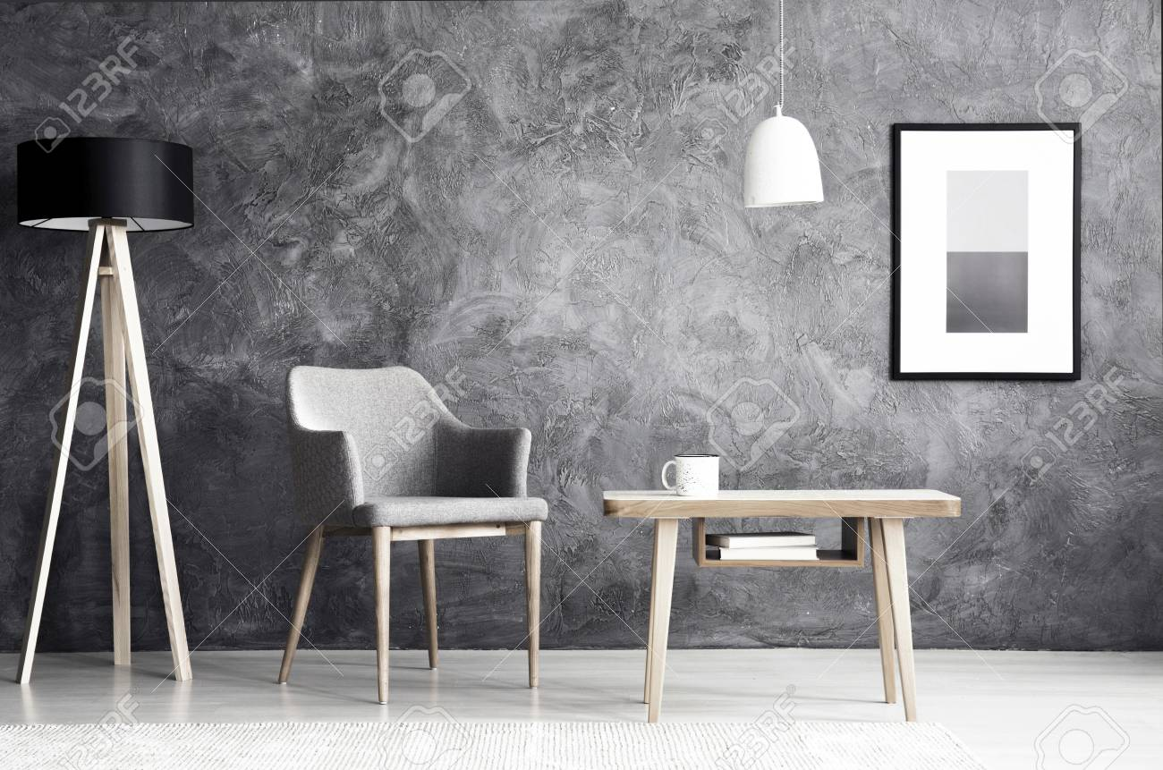 White lamp above wooden table next to grey armchair in living room foto de archivo white lamp above wooden table next to grey armchair in living room interior with poster on concrete wall aloadofball Image collections