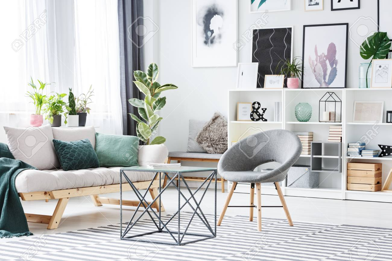 Metal Table Between Grey Chair And Sofa With Green Cushions In ...