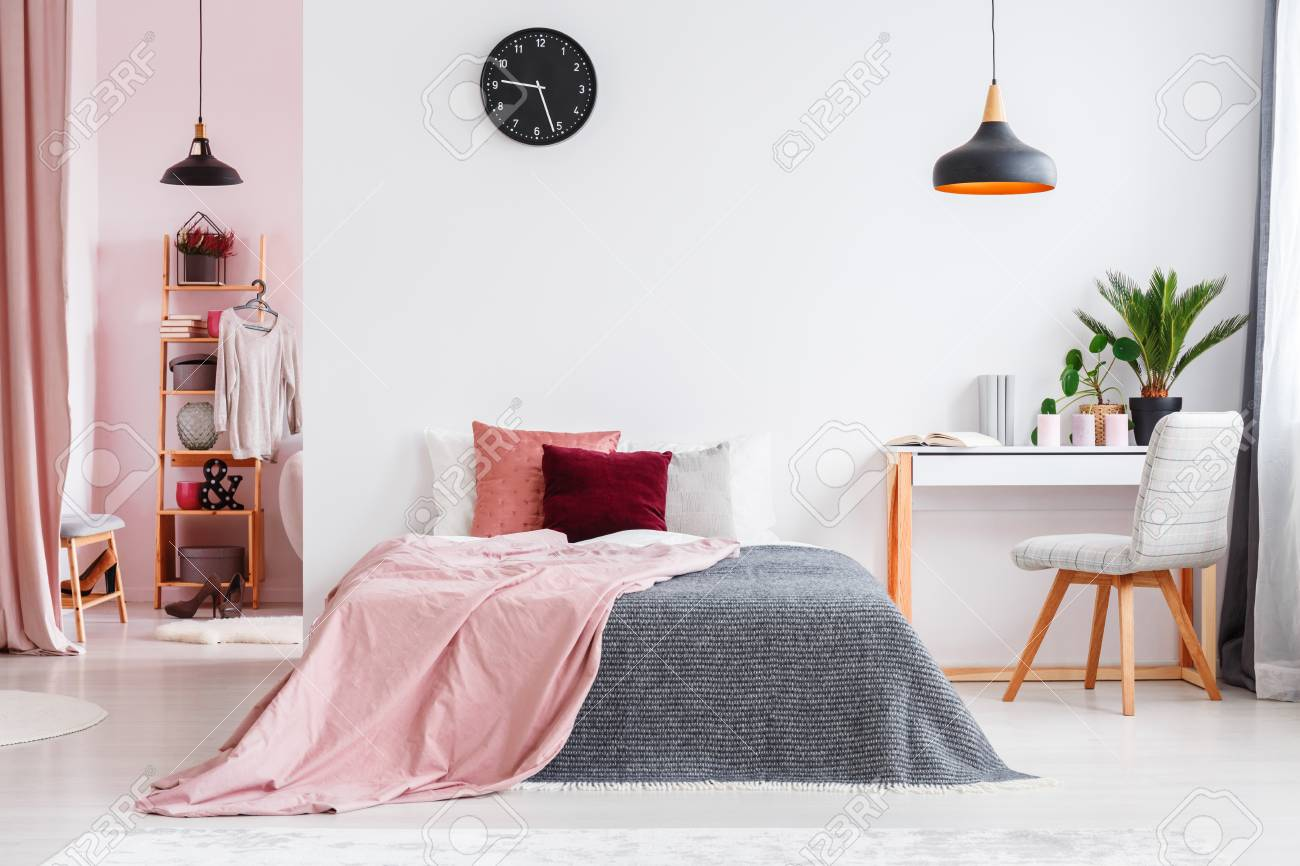 Pink blanket on bed next to desk and grey chair in bedroom interior..