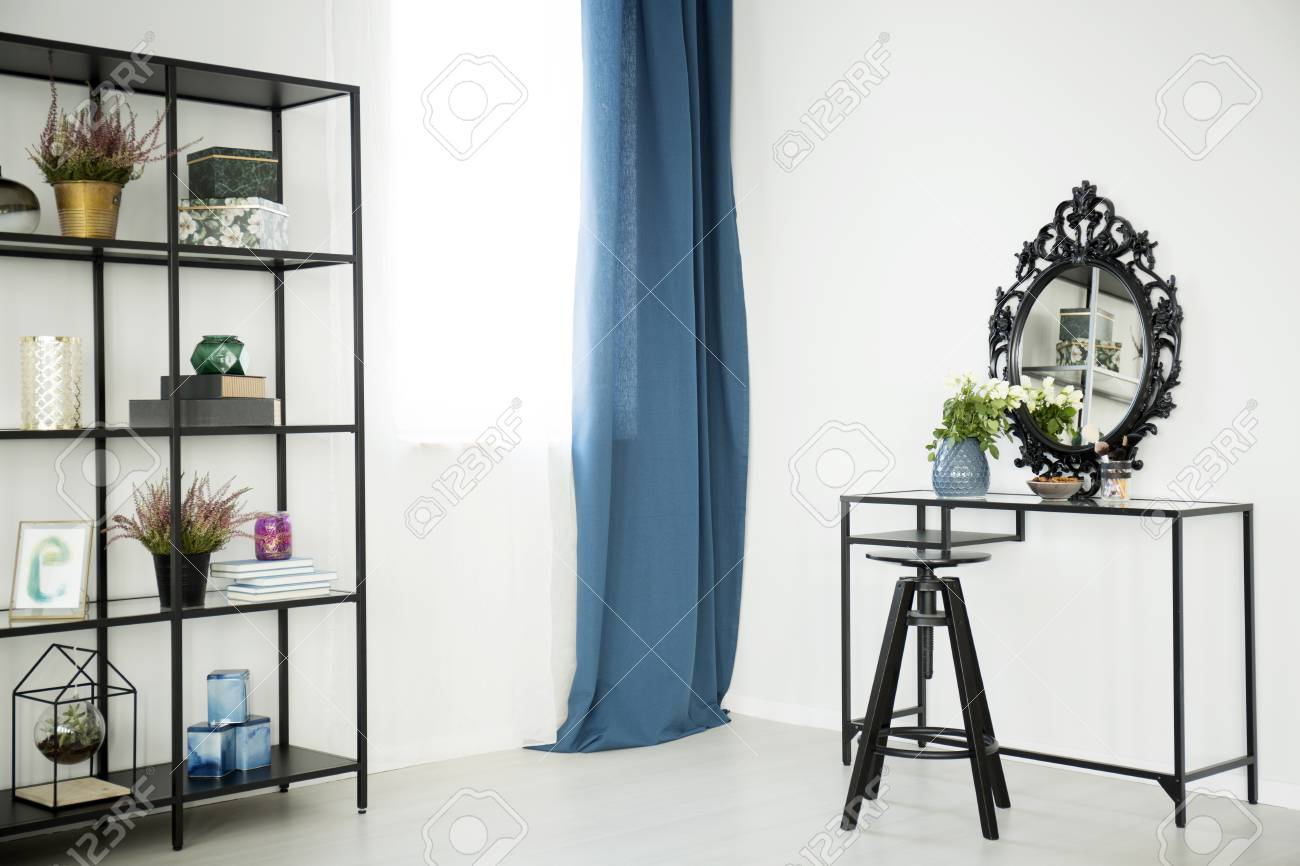 Stock Photo   White Flowers On Dressing Table With Decorative Mirror In  Sophisticated Interior With Blue Curtain