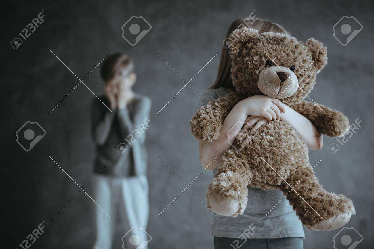 In the foreground kid holding a teddy bear in the background jealous crying brother - 95518401