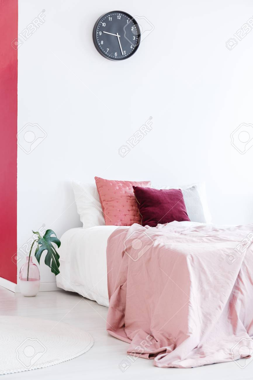 Pastel pink bedsheets on bed with cushions against white wall..