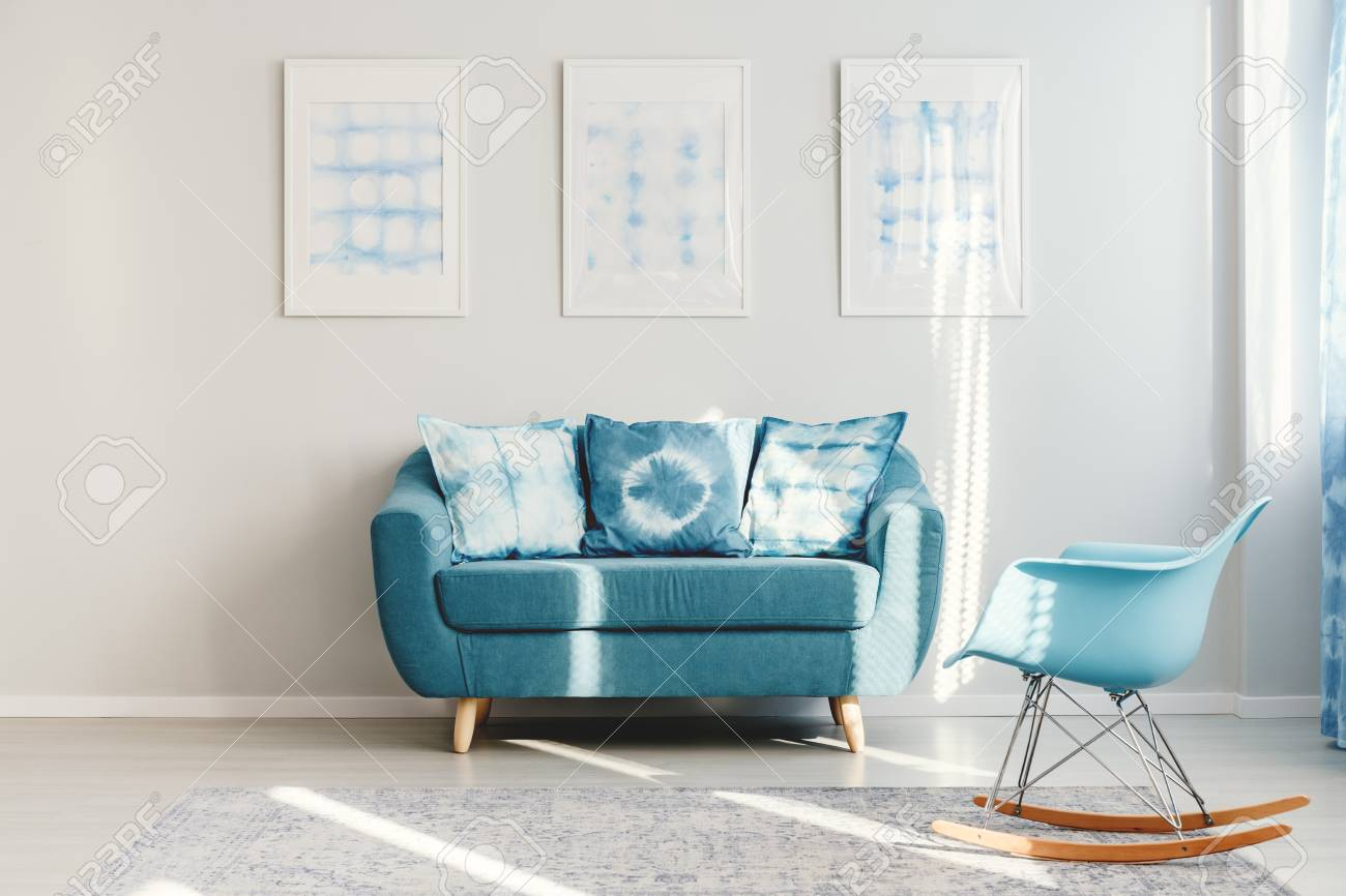 Blue Rocking Chair On Grey Carpet And Turquoise Couch With Patterned ...