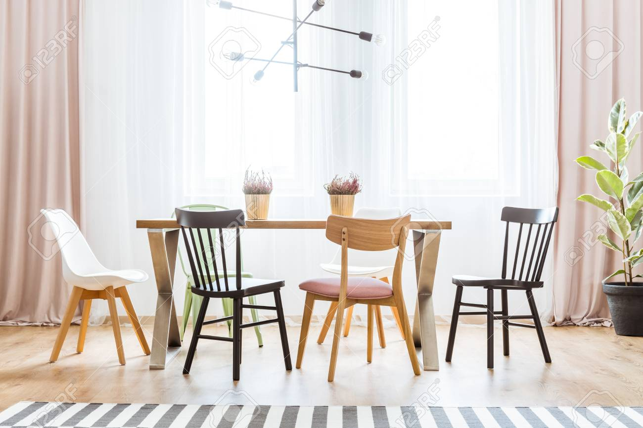 Wooden Chairs At Table With Heathers In Bright Pastel Dining Room
