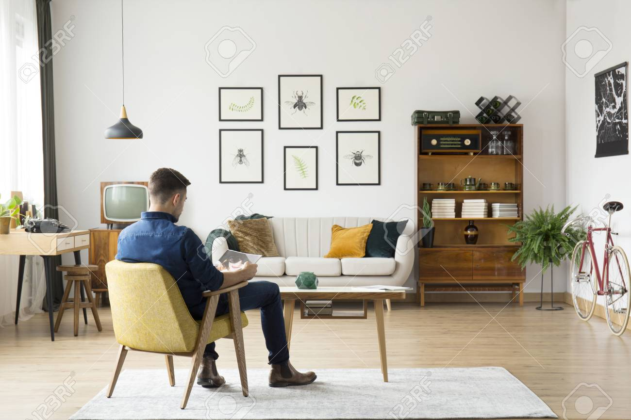 Man Sitting In Yellow Chair At Wooden Table In Retro Living Room ...