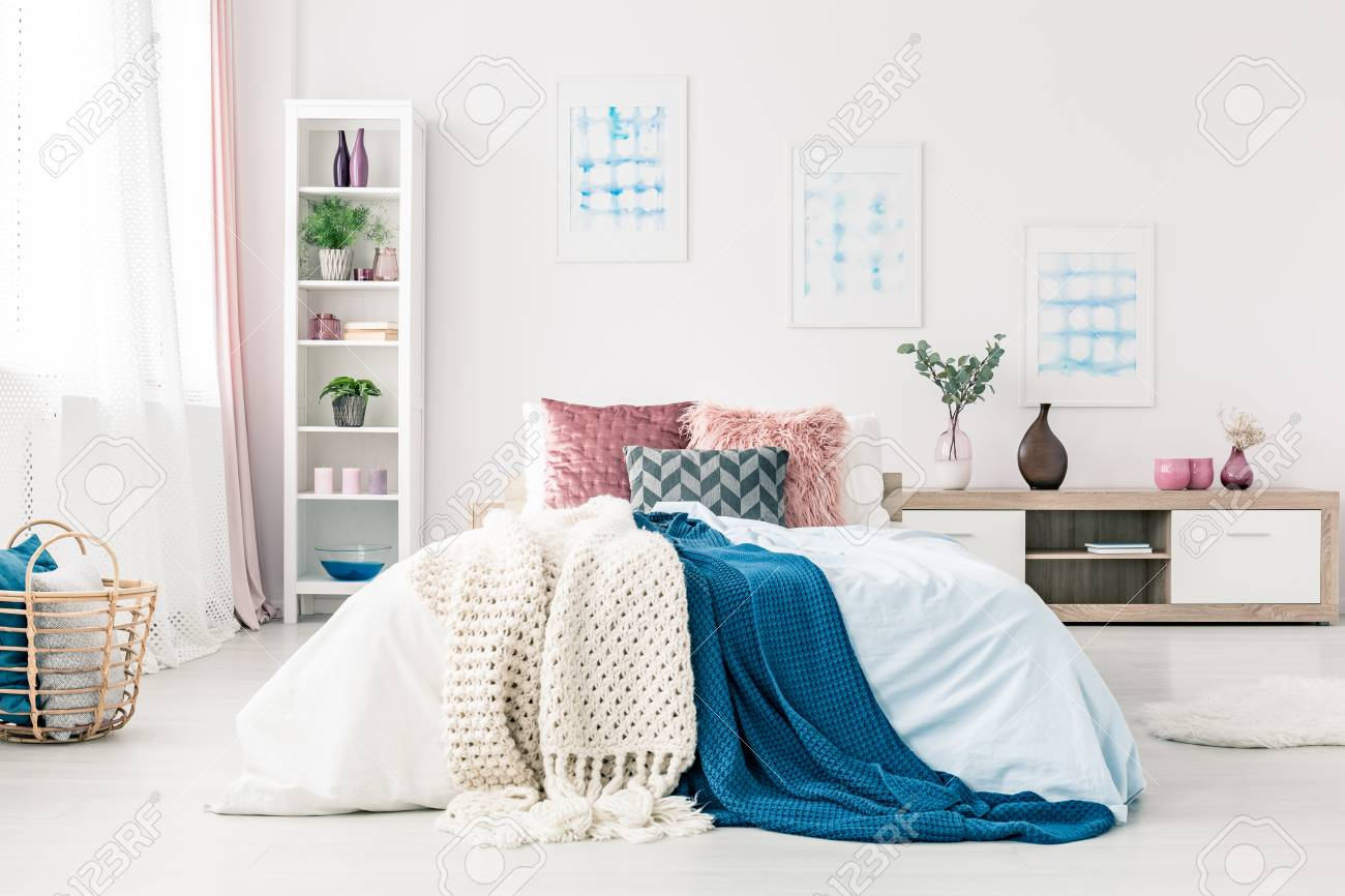 Blue blanket on bed with pink cushions in sophisticated bedroom..