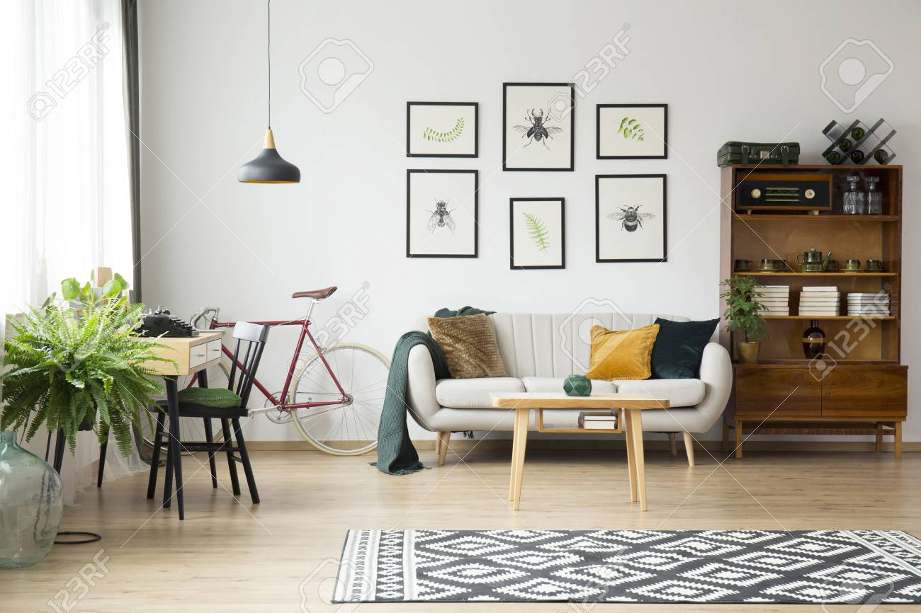 Patterned rug and fern in bright vintage living room interior..