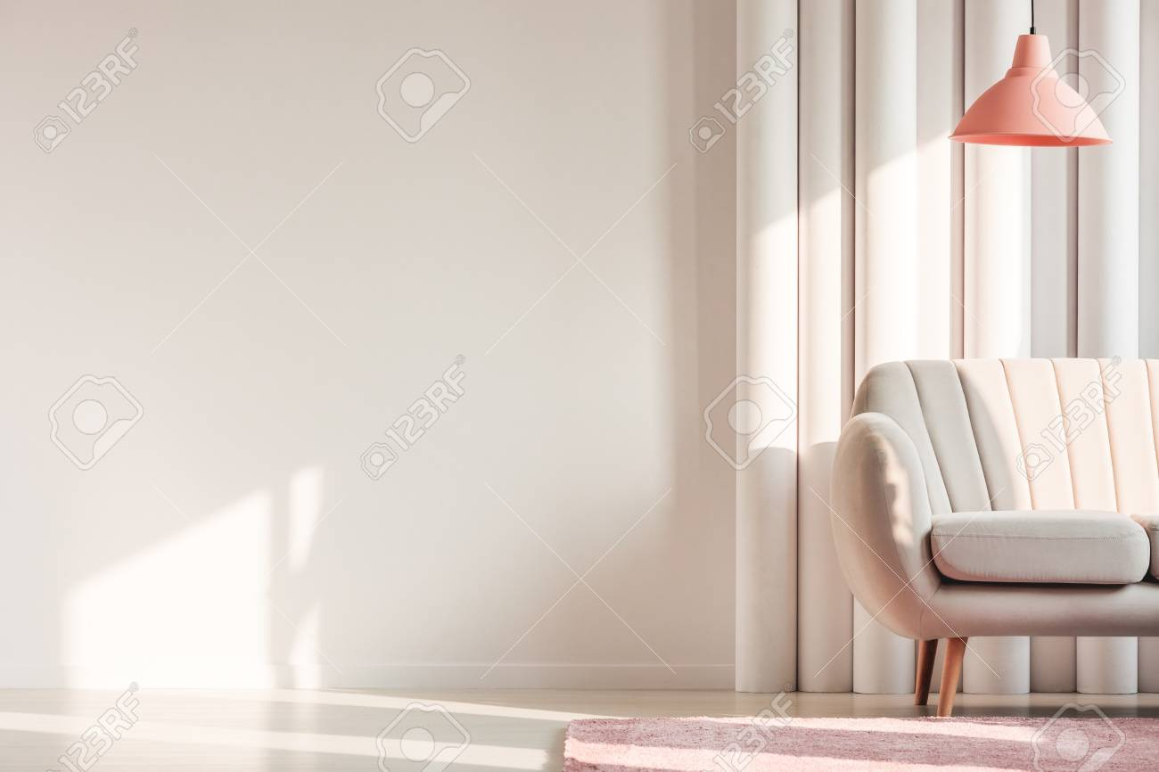 Peach lamp above beige couch and pink rug against plastic tubes in simple living room interior with copy space on white wall - 96674181